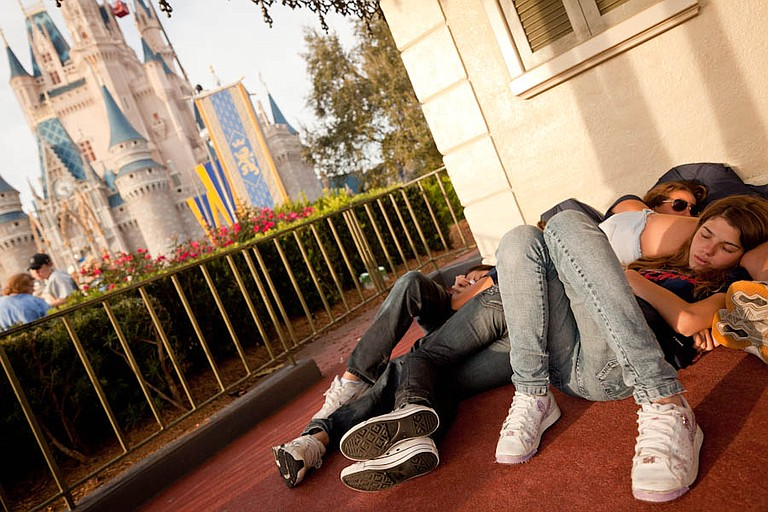 A couple of youths asleep in the Magic Kingdom. Orlando, Florida.