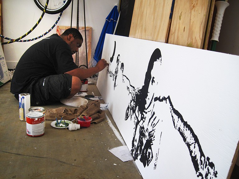 Charles Brice works on a panorama painting of his experiences in Afghanistan.