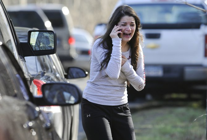 A woman waits to hear about her sister, a teacher, following a shooting at the Sandy Hook Elementary School in Newtown, Conn., about 60 miles (96 kilometers) northeast of New York City, Friday, Dec. 14, 2012. An official with knowledge of Friday's shooting said 27 people were dead, including 18 children. It was the worst school shooting in the country's history.