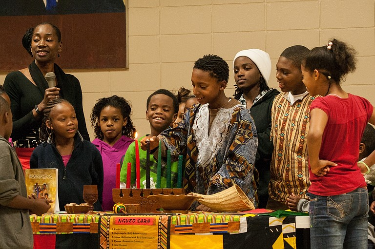 Local children gather to light the Kwanzaa candles at the Medgar Evers Community Center Thursday night.