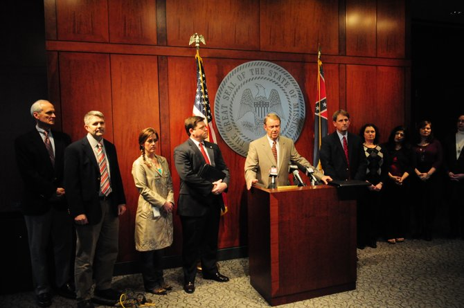 Mississippi Insurance Commissioner Mike Chaney (standing at podium), a Republican now in his second-term as insurance commissioner, started working on the Mississippi health-insurance exchange more than three years ago, before Bryant became governor.