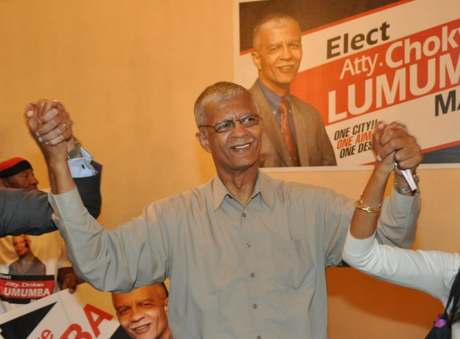 "Chokwe Lumumba holds his son and daughter's hands as he walks in the Clarion Hotel's ""Trinity II"" room upon winning the Democratic Primary."