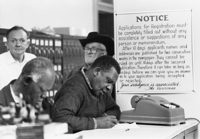 Black citizens fill out voter registration forms at the Courthouse under a sign warning them the applicants' names and addresses will be published in the newspapers. Hattiesburg, Forrest County, Mississippi, United States. 1964