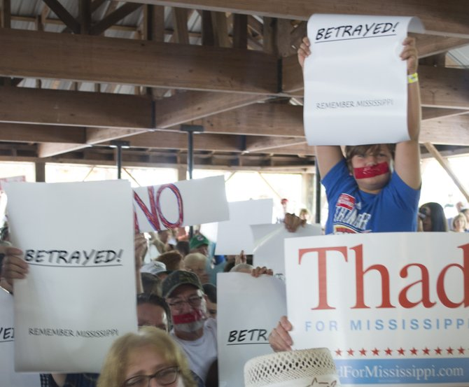 """Sen. Chris McDaniel's supporters brought signs to the Neshoba County Fair's 2014 political speeches that read """"betrayed"""" and """"RINO"""" (or Republican In Name Only) targeted at U.S. Sen. Thad Cochran."""
