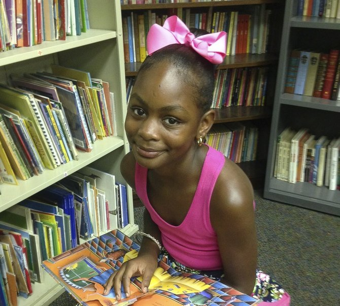 Cayden Taylor, 11, sits in the library of Operation Shoestring in Jackson.
