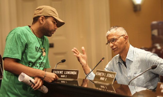 In this undated photo, then-Ward 2 Councilman Chokwe Lumumba (right) consults with his son, Chokwe Antar Lumumba, whose loss in this year's mayoral election, some believe, stymied the economic vision his father laid out before his death.