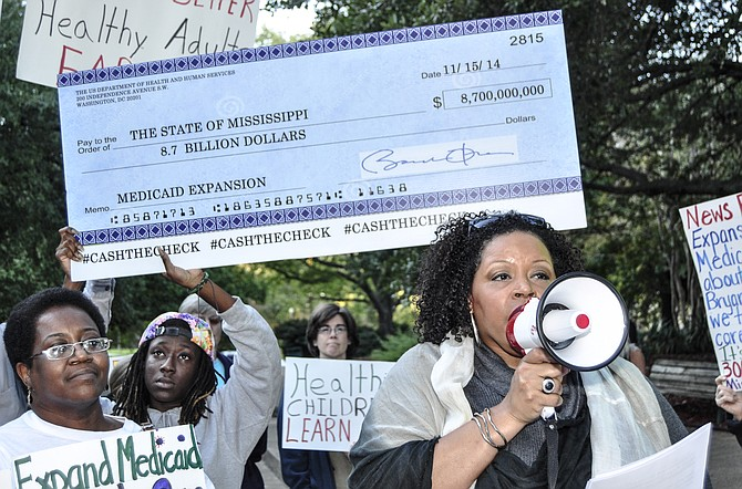 At a 2014 rally, demonstrators carried a large check for $8.7 billion that contained the signature of President Barack Obama to represent the amount the federal government would contribute if Mississippi loosened Medicaid eligibility requirements. File Photo.