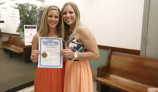 Tiffany Brosh (right) and Laurin Locke (left) pose with their marriage license at the Hinds County Courthouse on Monday after being denied their right to marry on Friday morning.