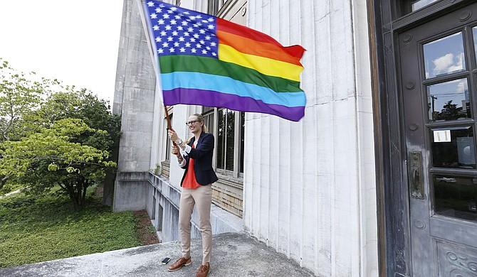 Lindsey Simerly waves a rainbow-themed American flag at the Hinds County Courthouse June 26 to celebrate a court ruling that legalized same-sex marriage nationally.