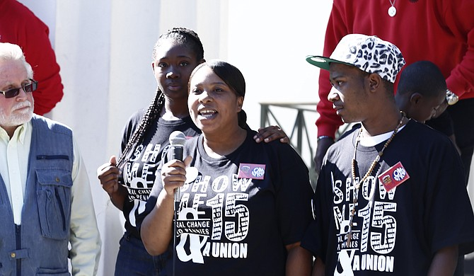 "Bill Chandler of the Mississippi Immigrants Rights Alliance (far left) stands on the steps of Jackson City Hall with local fast-food workers Cajania ""CoCo"" Brown, Kenyata McInnis and Tevin Tarrio (left to right)."