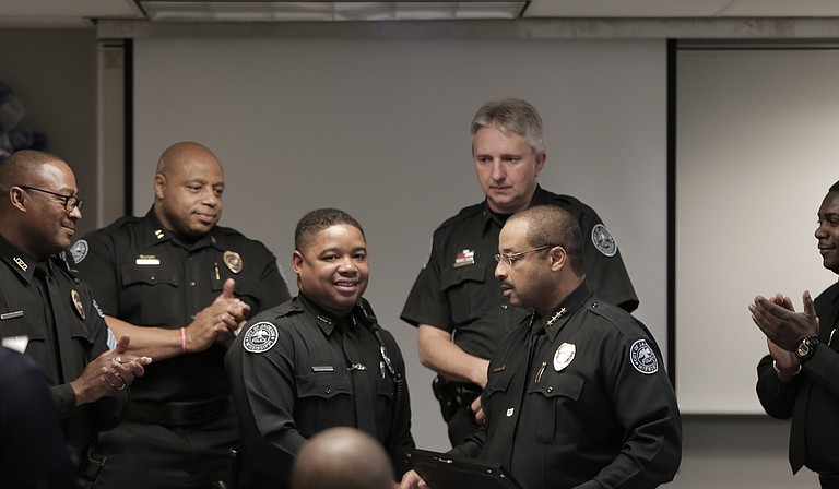 Officer Brandon Caston (center) was recently named Jackson Police Department's Officer of the Month for March for collaring two suspected carjackers when he was off duty. To his right, Police Chief Lee Vance presented him with an award.