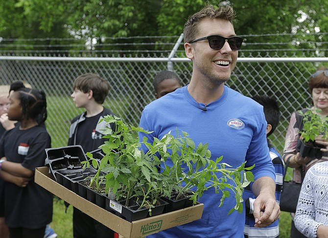 Lance Bass helps students plant seedlings in a community garden in Clinton.