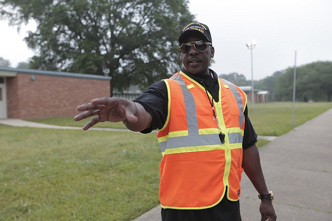 Sgt. Steve Collins, Jackson Public Schools Parent of the Year for 2016, helps McLeod Elementary School students in the carpool line.