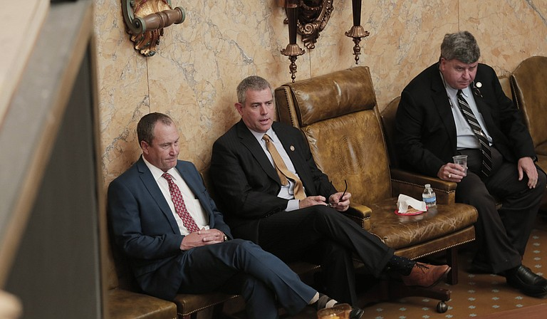Rep. Herb Frierson, R-Poplarville, (left) House Speaker Philip Gunn (center) and Speaker Pro Tempore Greg Snowden, R-Meridian, (right) wait at the front of the House chamber, while a bill is read.