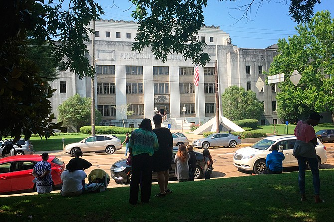 County employees and members of the public wait for the all-clear from Hinds County Sheriff's deputies as they search for explosives after a bomb threat Thursday morning.