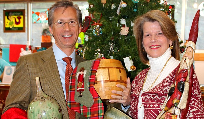 Mayo Flynt, the chairman of the board of trustees at the Mississippi Museum of Art, and Renee Flynt, a former president of the Craftsmen Guild of Mississippi, pose with items from the Chimneyville Crafts Festival. Photo courtesy Nancy Perkins