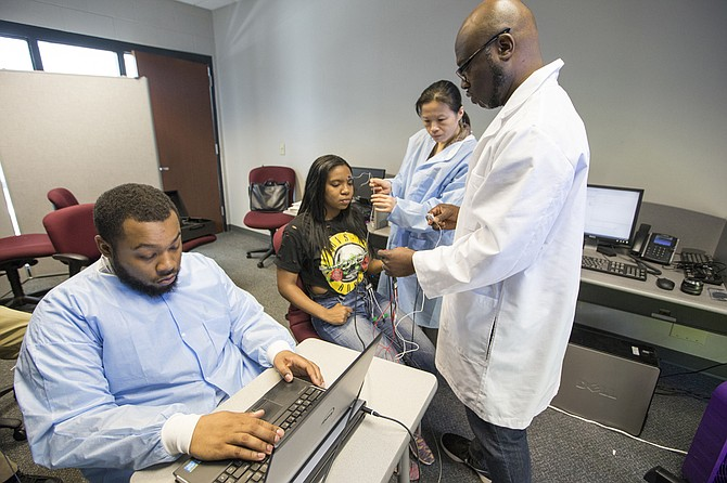 Byron D'Andra Orey (right), a JSU political science professor, is conducting experiments to examine unconscious bias in African Americans. Seated at the computer is his son, Kalen Orey, who helps with the project, while JSU criminal-justice professor Yu Zhang wires up student Ananda Collins.