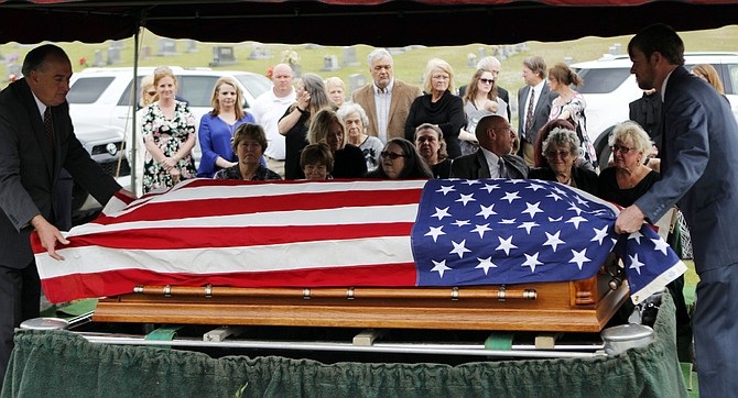 The flag-draped casket of Stanley Dearman, the former editor of The Neshoba Democrat newspaper in Philadelphia, Miss., is placed before his family, Tuesday, Feb. 28, 2017. Dearman edited the Democrat for 34 years. (Mike Robertson/The Neshoba Democrat, via AP)