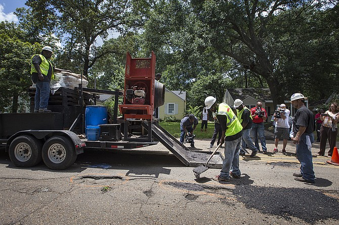 Workers for Gluckstadt-based Mega Technologies, LLC fill potholes on Northview Drive in Fondren. The potholes were marked with an orange circle. The company uses a polymer-based product rather than asphalt.