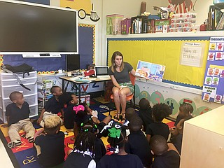 "North Jackson Rotary Club Member and ""Between the Lions"" coordinator Jenny Price (back) reads to kids at Walton Elementary School for the project. Photo courtesy Clinton Smith"