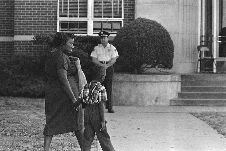 An African American first grader clutched his mother's hand as he arrived for the first day of school at previously all-white Davis Elementary School in Jackson on Sept. 14, 1964. Black students could voluntarily integrate white schools back then, but local public schools would not fully integrate until 1970. (AP Photo)