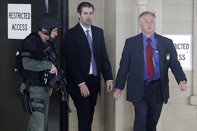 In this Monday, Dec. 5, 2016, file photo, former South Carolina officer Michael Slager (center) walks from the Charleston County Courthouse under the protection of the Charleston County Sheriff's Department after a mistrial was declared for his trial in Charleston, S.C. Photo courtesy AP/Mic Smith