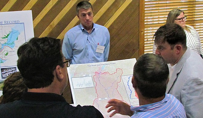 Community members listen as project engineer Brett Mendrop (center, striped shirt) describes the One Lake Flood and Drainage Control project.