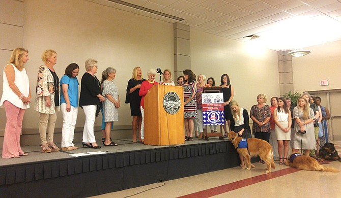 Members of the Mississippi Federation of Republican Women and the Mississippi Center for Violence Prevention stand on the stage during a press conference about human trafficking.
