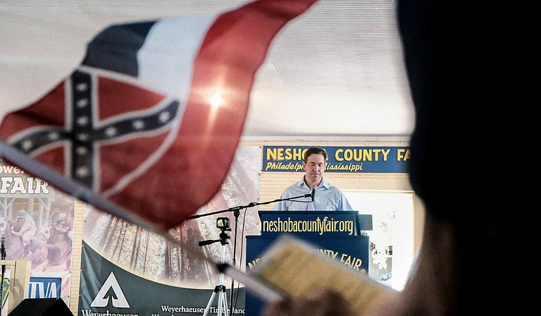 As Republican U.S. Senate candidate Chris McDaniel speaks at the Neshoba County Fair in Philadelphia, Miss., on Aug. 2, 2018, a supporter holds up a replica of the Confederate emblem-bearing Mississippi flag, which McDaniel opposes changing.