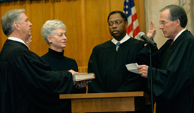 Charles Pickering, left, recites the oath of office, as he is sworn on to the 5th U.S. Circuit Court of Appeals on Friday, Jan. 16, 2004, at the federal courthouse in Jackson. Giving the oath is fellow Appeals Judge Rhesa Barksdale, right, while Pickering's wife, Margaret Anne Pickering and Judge Henry T. Wingate watch.