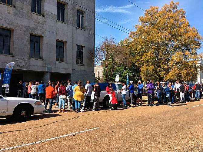 Several dozen people stood in line outside the Hinds County Courthouse in Jackson, Miss., on Saturday, Nov. 24, 2018, waiting to cast absentee ballots in a U.S. Senate election runoff between Republican Sen. Cindy Hyde-Smith and Democrat Mike Espy. Photo by AP/Emily Wagster Pettus