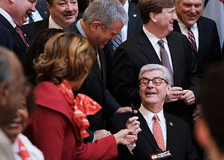 Surrounded by proud lawmakers, Mississippi Gov. Phil Bryant holds up a pen he used to sign the Mississippi Broadband Enabling Act in the State Capitol rotunda on Jan. 30, 2019.