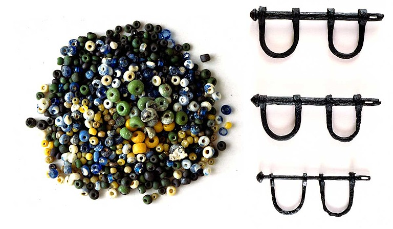 Tiny, colorful glass beads (left) found on the wreckage site of the Henrietta Marie slave ship were made in Europe. They were often used to trade for slaves. Aboard slave ships, Africans were forced to wear iron shackles (right), huddled below decks in the heat. Photo courtesy Corey Malcom/MDAH