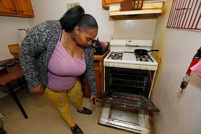 Destiny Johnson shows the broken door to her oven that she uses string to hold together, in her apartment in Cedarhurst Homes, a federally subsidized, low-income apartment complex in Natchez, Miss. The complex failed a health and safety inspection in each of the past three years. Upset with conditions, Johnson moved out in late March. Photo by Rogelio V. Solis via AP