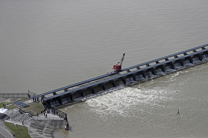 In this March 8, 2018 file photo workers open the gates of the Bonnet Carre spillway, a river diversion structure, which diverts water from the rising Mississippi River, left, to Lake Pontchartrain, in Norco, La. The Army Corps of Engineers' New Orleans office is asking to open the historic flood control structure above New Orleans for the second time in one year. The National Weather Service says continued rains in the Midwest and Ohio Valley and floodwaters from the upper Mississippi River are heading down the Mississippi. File Photo by Gerald Herbert via AP