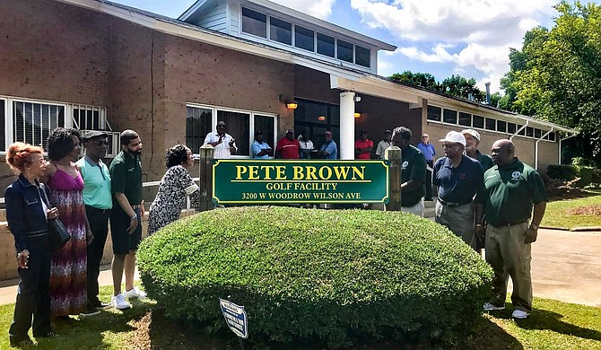 Margaret Brown (center left), Pete Brown's wife, unveils a new sign, renaming Sonny Guy Golf Course to Pete Brown Golf Facility on May 23.