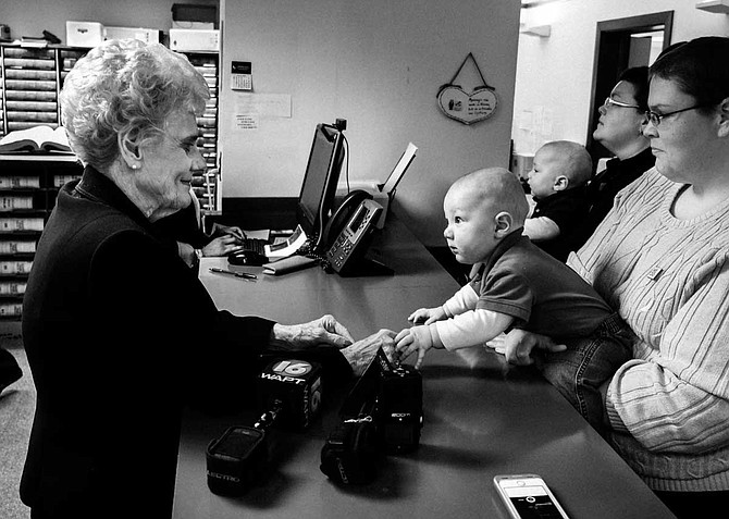 Andrea Sanders (right) holds 8-month-old Owen as he reaches across the counter to touch then-Hinds County Circuit Clerk Barbara Dunn (left). Sanders and Becky Bickett, now her wife, were at the Hinds County Courthouse applying for marriage licenses with their twin boys in March 2014, when marriage was still illegal for same-sex couples.