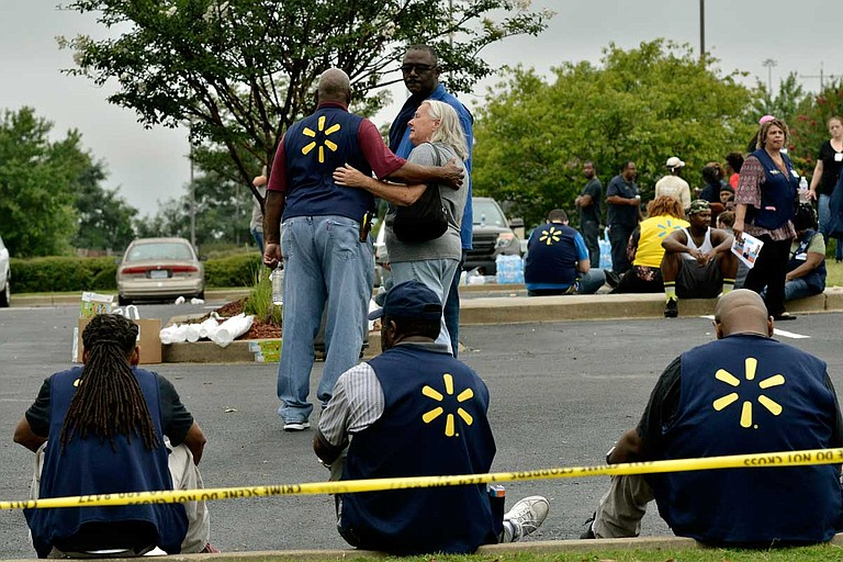 Law enforcement personnel and employees gather in a nearby parking lot after a shooting at a Walmart store Tuesday, July 30, 2019 in Southaven, Miss. Photo by Brandon Dill via AP