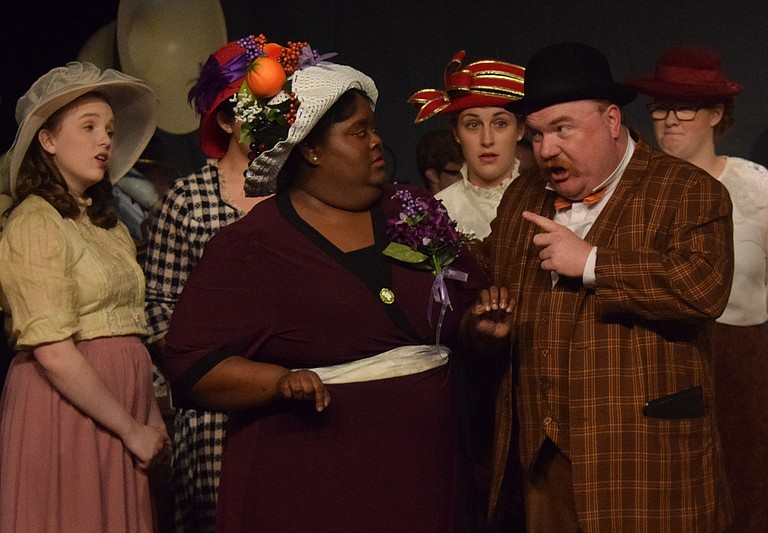 """In Black Rose Theatre's production of """"The Music Man,"""" Brittany Butler (left) stars as the mayor's wife, Eulalie Shinn, and Chris Roebuck (right) stars as con artist Harold Hill. The cast includes more than 30 people in the ensemble. Photo by Andrew Overton"""