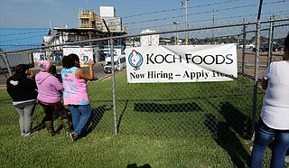 Friends, coworkers and family watch as U.S. immigration officials raid several Mississippi food processing plants, including this Koch Foods Inc., plant in Morton, Miss., Wednesday, Aug. 7, 2019. The early morning raids were part of a large-scale operation targeting owners as well as undocumented employees. Photo by Rogelio V. Solis via AP