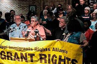 At a press conference on Aug. 8, Father Jeremy Tobin, a Catholic priest, puts his hand on the shoulder of Mississippi Immigrants Rights Alliance organizer Luis Espinoza, who has been working with immigrant families affected by the Aug. 7 ICE raids in Mississippi. Photo by Ashton Pittman
