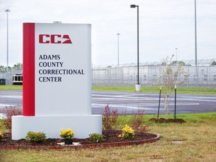 The cause of riot at a private federal prison Adams County is disputed.
