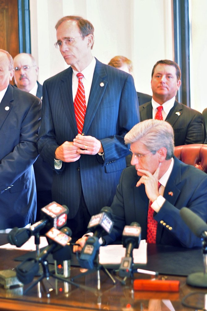 Gov. Phil Bryant (sitting) signed the legislation to implement voter ID in Mississippi.