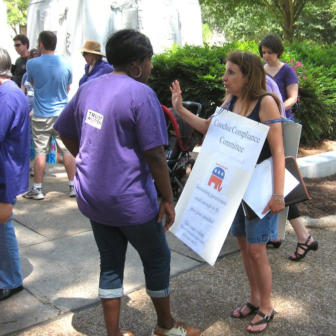 "Protesters talk at a rally in Jackson Saturday to protest the ""war on women."""