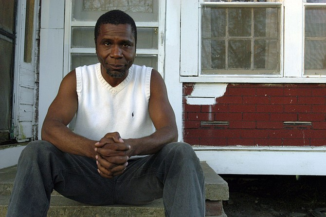 John Ellis Ishmael Briggs Be sits outside his family home in  Roxie, Miss., that his parents had to protect from the Ku Klux Klan in the 1960s because his father, Rev. Bennie Clyde Briggs, tried to protect and help local black people. The home has a bullet hole where the Klan shot from the outside into the wall over where Briggs Be's little sister slept. Photo by Kate Medley