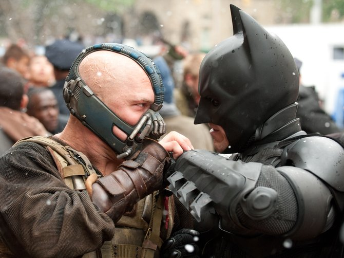 "Batman's new nemesis, Bane (Tom Hardy), challenges the caped crusader (Christian Bale, right) in ""The Dark Knight Rises."""