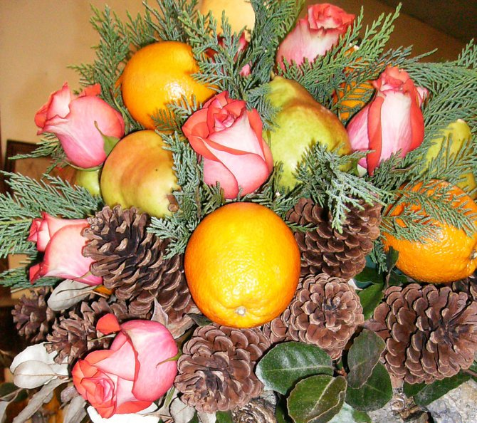 Incorporating pine cones and fruit can take more summery flowers, such as pastel roses, into fall.