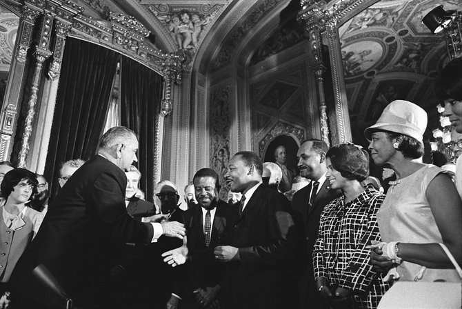 Martin Luther King Jr. meets with then-President Lyndon Johnson following the signing of the Voting Rights Act in 1965.