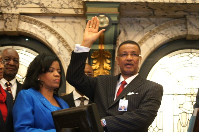 Sollie Norwood (right), with wife, Joan, looking on, is sworn in as Jackson's newest state senator.