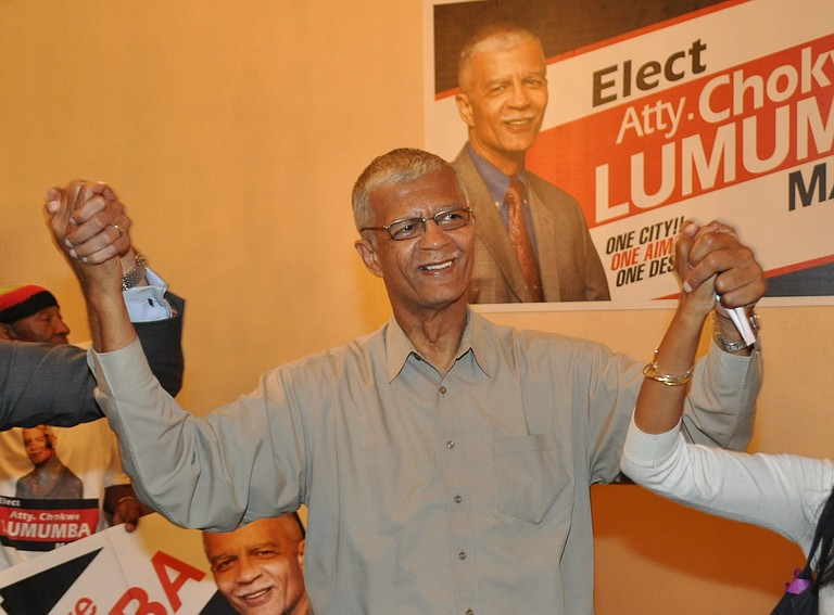 """Chokwe Lumumba holds his son and daughter's hands as he walks in the Clarion Hotel's """"Trinity II"""" room upon winning the Democratic Primary."""